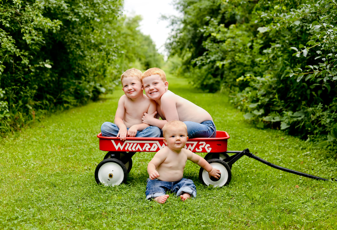 Rustic child portraits with red wagon and just blue jeans on, by Kelsey Jorissen Photography